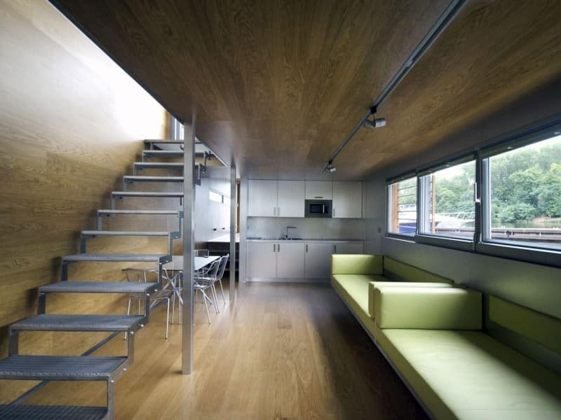 This houseboat includes a stainless steel staircase that's simple and clean. It has clear glass on the side and space underneath is wide enough to place a dining set.