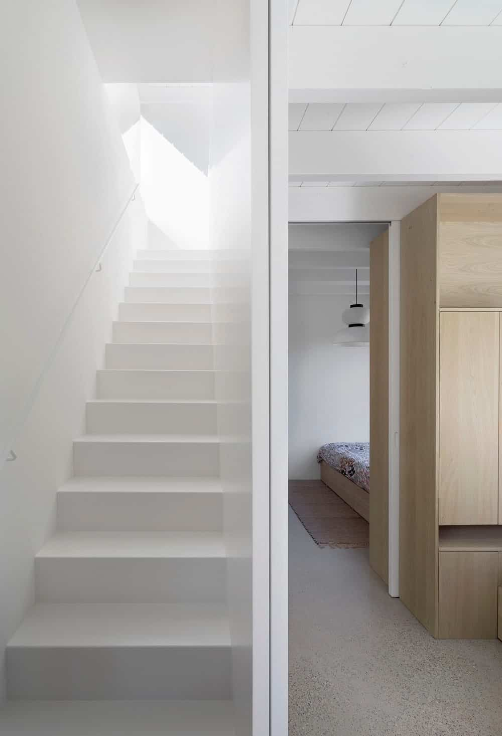 An all-white staircase with a thin metal handrail that's very easy in the eyes. You won't even notice its narrowness and sleekness.
