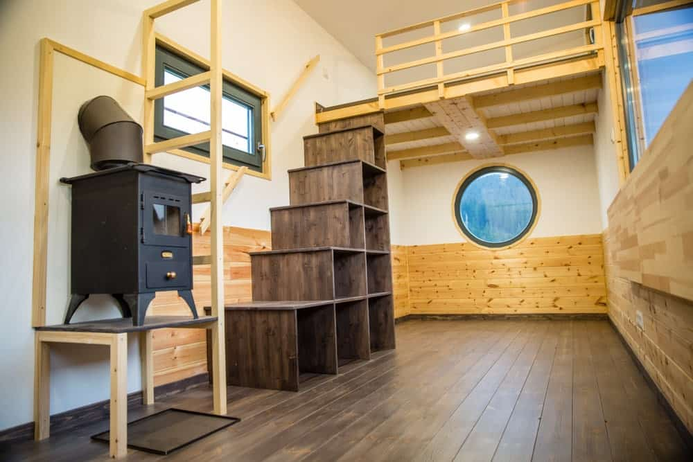 This dark wooden staircase with light wood handrail has bigger steps than the usual. It creates spacious cube shelves that are perfect for your stuff.