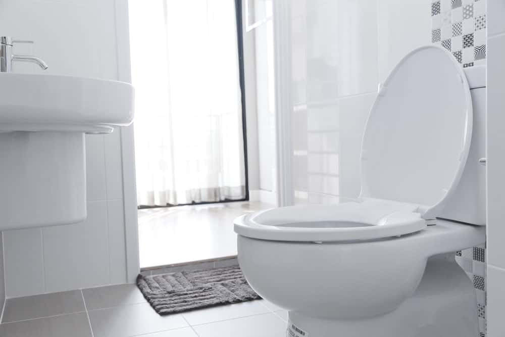 Toilet in a white powder room.
