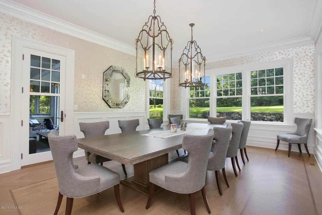 This elegant dining room has matching gray wingback dining chairs surrounding a large dark wooden table that fits with the hardwood flooring that is contrasted by the white wainscoting of the patterned walls.