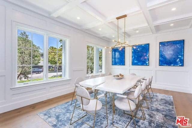 The light hardwood flooring of this formal dining room is covered with a bluish area rug that makes the white dining set stand out. This is mirrored by the blue artworks on the white walls.