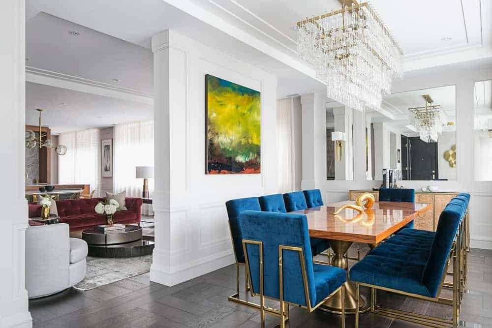 The blue velvet chairs surrounding the sleek wooden dining table are the highlight of this dining room with stark white walls accented with a colorful painting on one side and mirrors on the other.