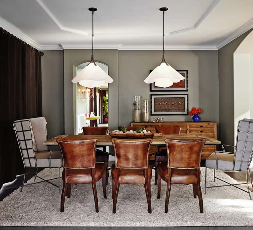 The light gray area rug is nice background for the contrasting brown leather chairs surrounding the wooden dining table that is topped with a pair of brilliant flower-shaped pendant lights hanging from the white tray ceiling.