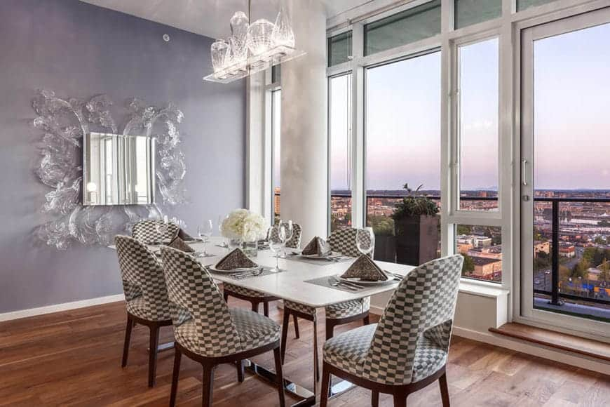 The checkered patterned dining chairs surrounding the modern dining table are the highlight of this elegant dining room that is accented with an amazing overlooking view of the city through tall glass windows.