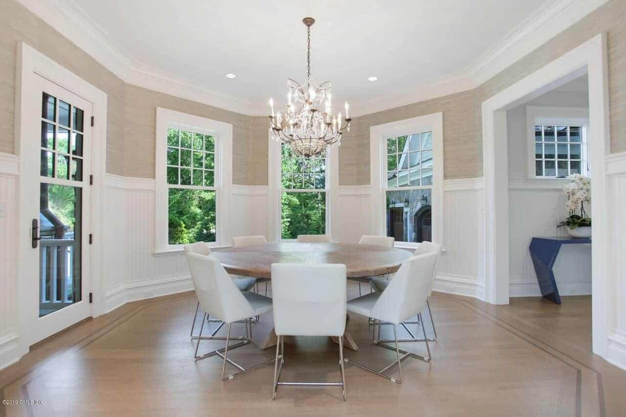 The round wooden dining table is surrounded by modern white chairs that stand out against the hardwood flooring but complements the white wainscoting of the walls illuminated by an elegant chandelier.