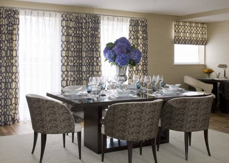 The dark patterned and cushioned dining chairs match with the patterned curtains of the tall windows that bring in natural light to the sleek black dining table adorned with blue flowers in a vase for a centerpiece.