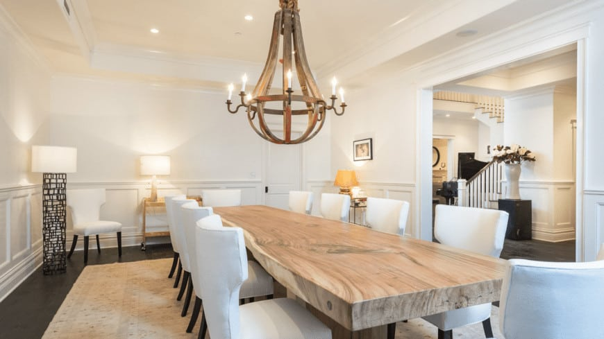 The thick butchers block top of the dining table is paired with white cushioned wing back chairs with dark legs that blend in with the dark hardwood flooring complemented by a large brass chandelier.