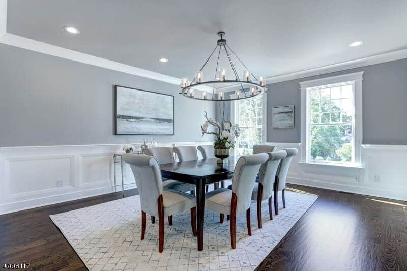 There is a farmhouse style round chandelier hanging from the light gray ceiling that matches with the light gray wall accented with white wainscoting. The cushioned dining chairs also match this light gray hue.
