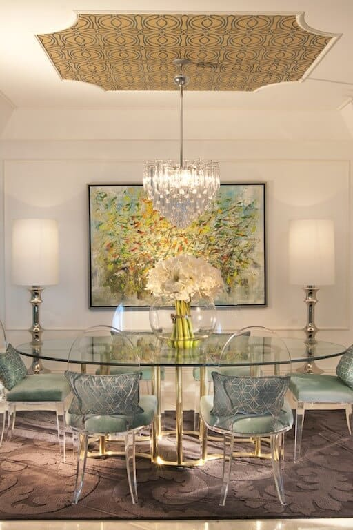 The round glass table is matched with see-through plastic oval backed dining chairs that is complemented by the golden legs of the table and the old rose hue of the area rug that contrasts the crystal chandelier.
