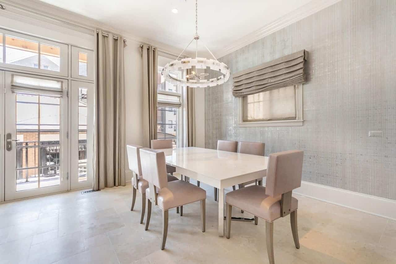 A white circular modern chandelier hangs over the white modern table surrounded by modern light gray chairs complemented by the wallpaper of the walls lightened by the tall windows and French glass doors.