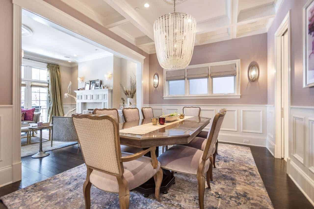 The dark hardwood flooring is topped with a camouflage patterned area rug under a dining set of wooden dining table matched with gray cushioned dining chairs matching with the gray walls that make the crystal lighting of the tray ceiling stand out.