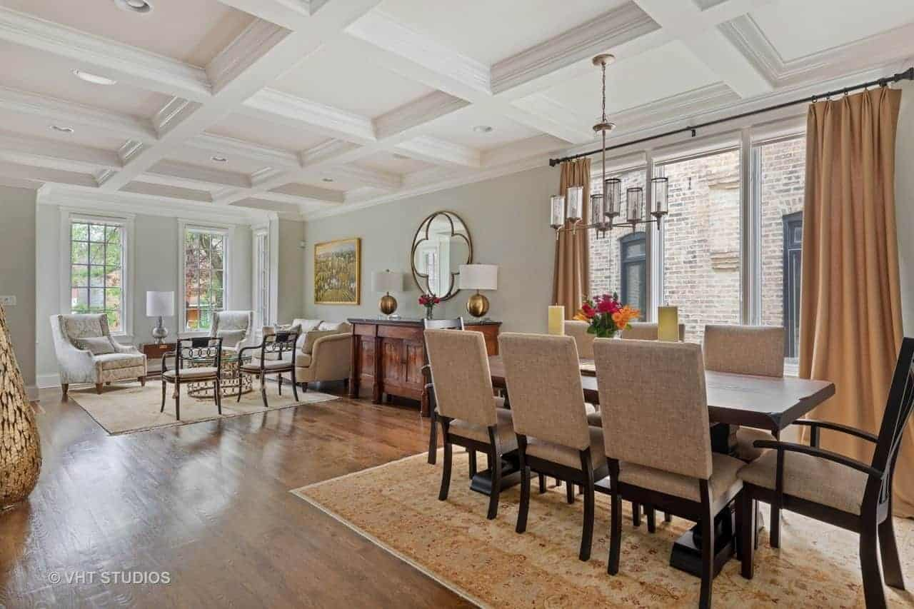 This dining area is part of a great room that also contains the living room within its hardwood flooring and white coffered ceiling. The dining area is placed by a large window that illuminate the wooden dining table and its gray cushioned chairs.