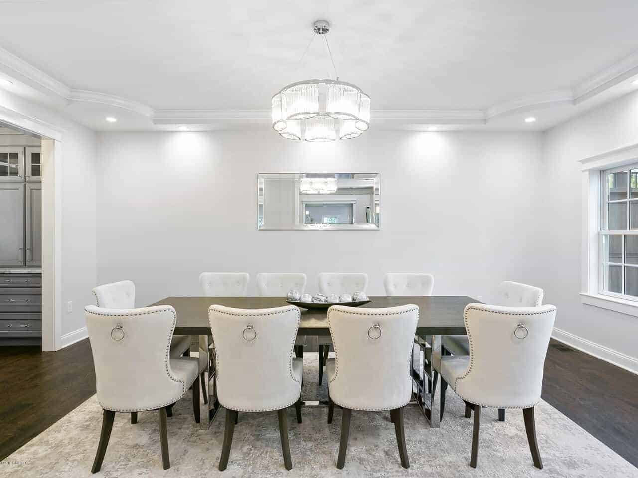 This is a formal white dining room with a white tray ceiling and walls contrasted by the dark hardwood flooring that matches with the elegant dark wooden dining table surrounded by white leather cushioned wing back chairs.