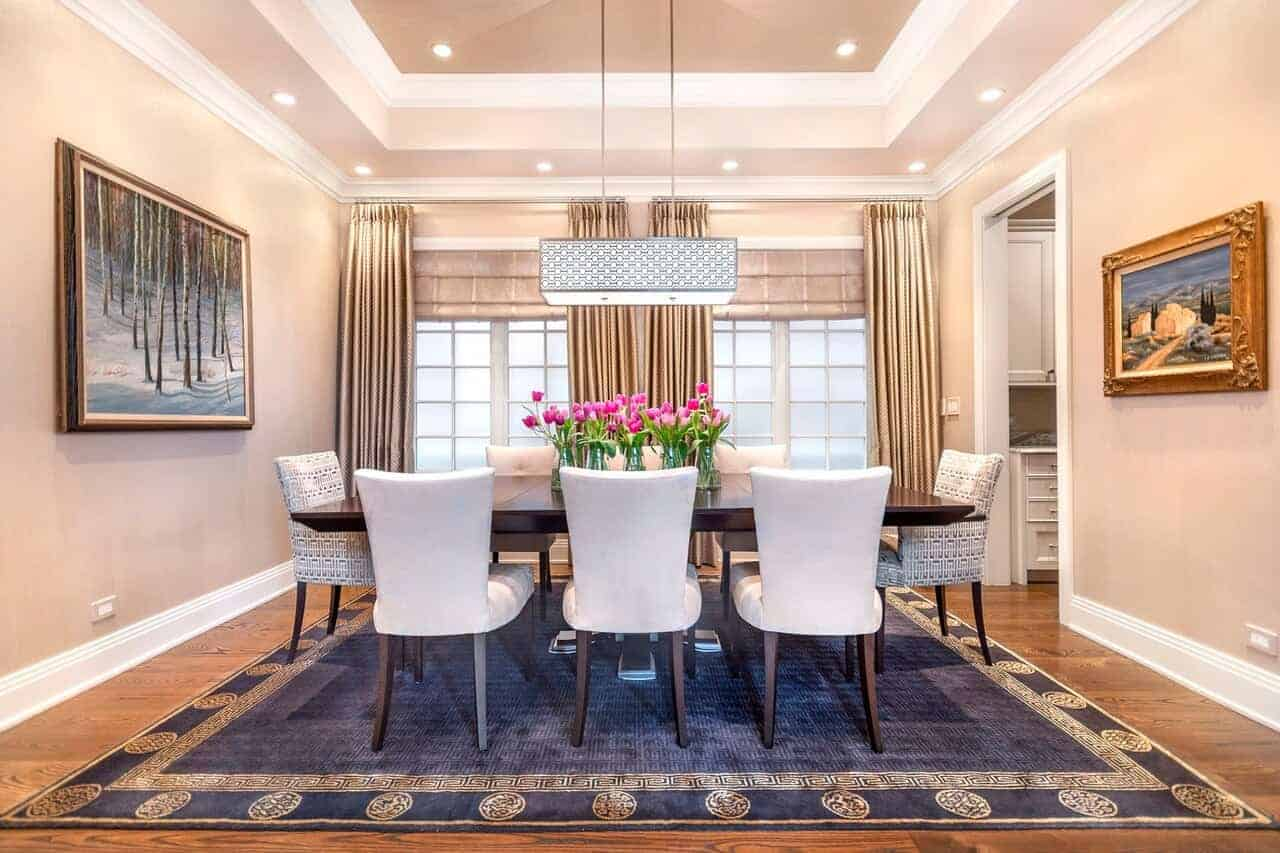 This charming Transitional-Style dining room has a beautiful blue patterned area rug covering most of the hardwood flooring. It contrasts the white cushioned dining chairs surrounding the dark wooden table.