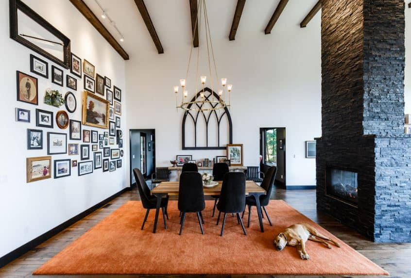 This charming and cozy dining area has a high white shed ceiling that has exposed wooden beams supporting a simple chandelier over the wooden table and its black velvet chairs that match with the black fireplace.