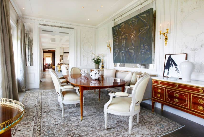 The white leather oval backed dining chairs are matched with the white walls that are accented with a dark painting flanked by golden wall-mounted lamps illuminating the redwood table.