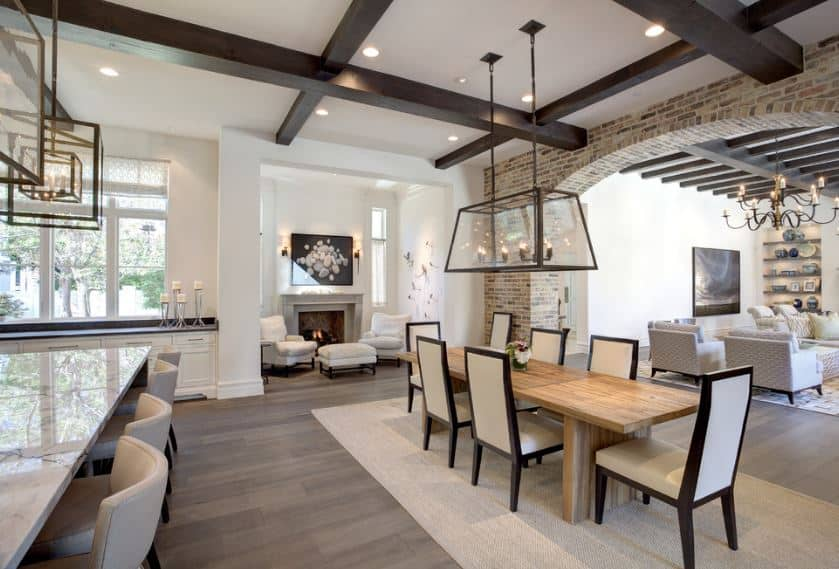 This charming dining area is part of a great room that also contain the living room and kitchen within its hardwood flooring and white ceiling that has exposed wooden beams that pairs with the framed of the chairs.