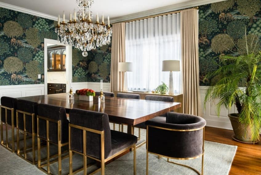 The walls of this dining room is dominated by a green wallpaper with patterns of flowers on it contrasted by white wainscoting that makes the black velvet chairs stand out as well as its dark wooden dining table.
