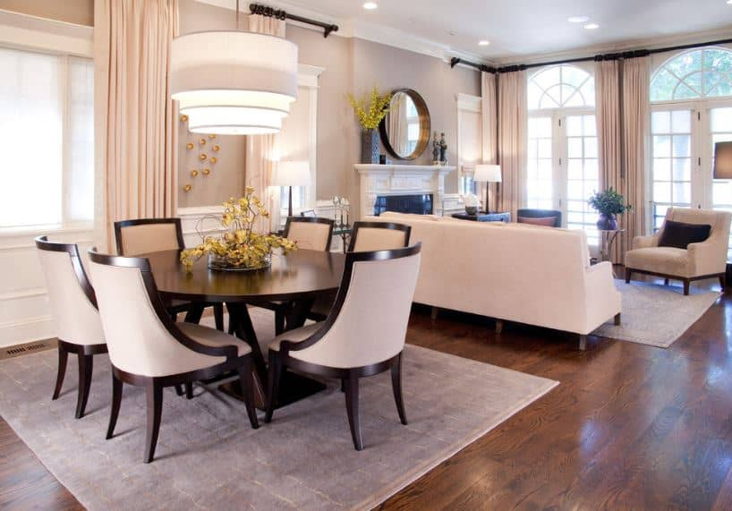 This small dining area has a dark wooden round table surrounded by white cushioned dining chairs with dark wooden frames matching with the hardwood flooring that is adorned with a gray area rug.