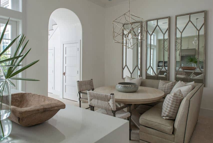 This small dining area has an L-shaped light gray leather cushioned bench that has a booth style to it. This is paired with a round light wood table and a couple of rustic woven wicker chairs.