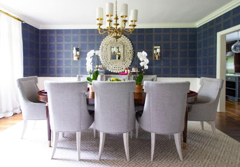 The checkered wallpaper of the walls are contrasted by the white wainscoting that complements the light gray cushioned wing back chairs surrounding the elliptical redwood table topped with a golden chandelier.