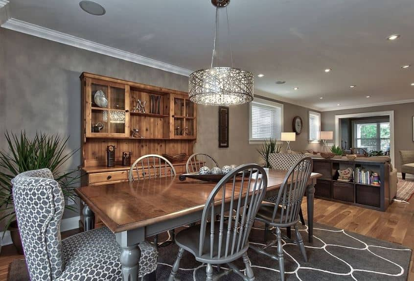 The gray slat-backed chairs are paired nicely with a couple of cushioned wing back chairs on each head of the brown wooden table over the dark gray patterned area rug of the hardwood flooring.