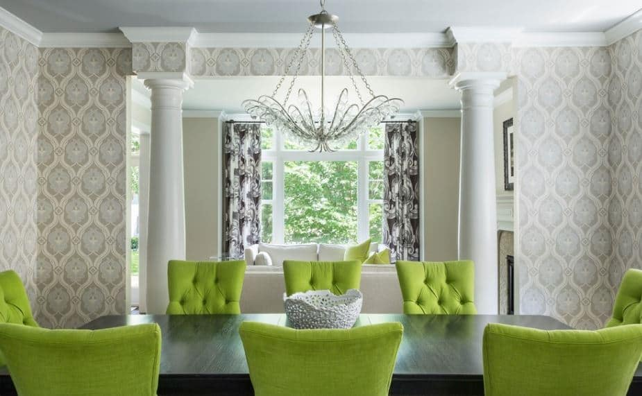 The brilliant avocado green cushioned dining chairs are the highlight of this dining room that has a black wooden dining table that contrasts the light gray patterns of the wallpaper.