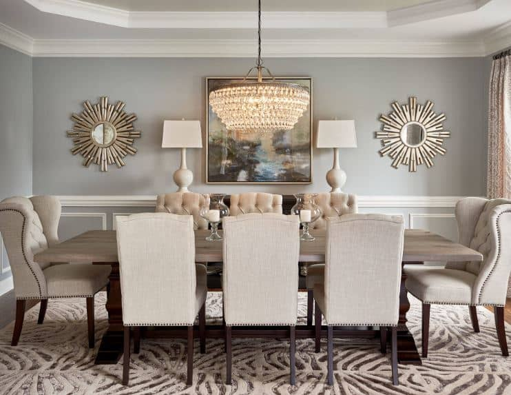 The light gray walls of this formal dining room is adorned with a colorful painting that is flanked by table lamps and a couple of sun-shaped mirrors that pair well with the elegant crystal chandelier hanging over the wooden table.