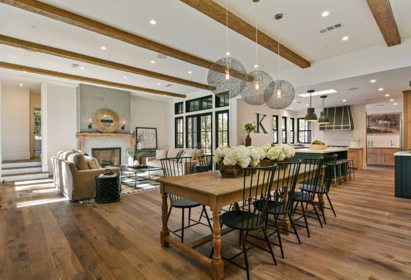 The three pendant lights are enclosed in rustic spherical covers that matches well with the black slat-backed chairs of the wooden table that blends in with the hardwood flooring and the exposed wooden beams of the white ceiling.