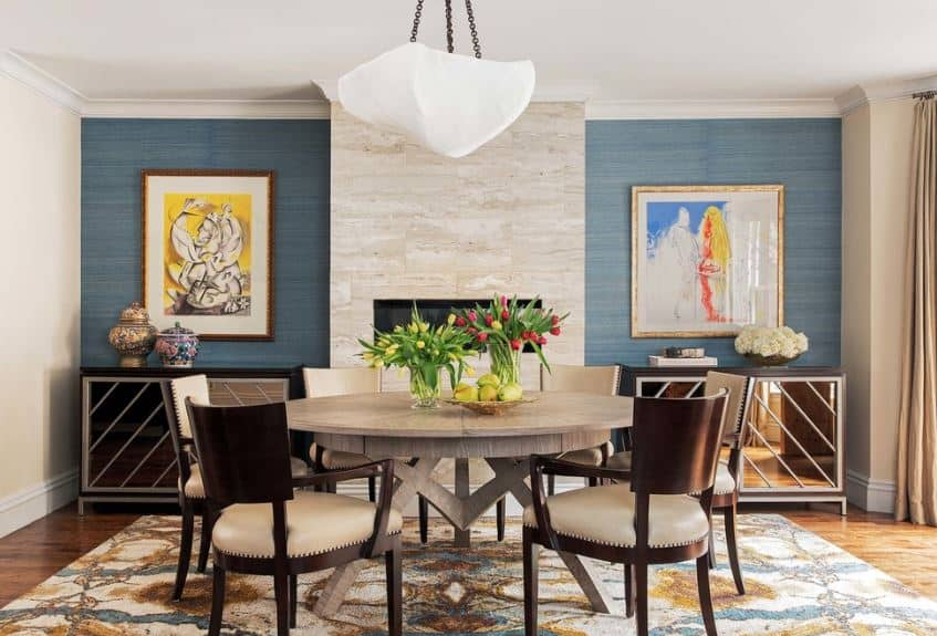 The green walls flanking the modern fireplace is a nice background for the round wooden table and its wooden chairs with beige seat cushions. that are complemented by the colorful area rug over the hardwood flooring.