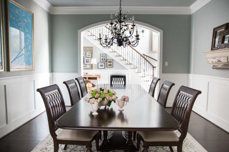 A simple but classic dining room with crown molding and wainscoting, eight-seater dining set with an oriental rug covering the hardwood flooring and a black vintage chandelier.