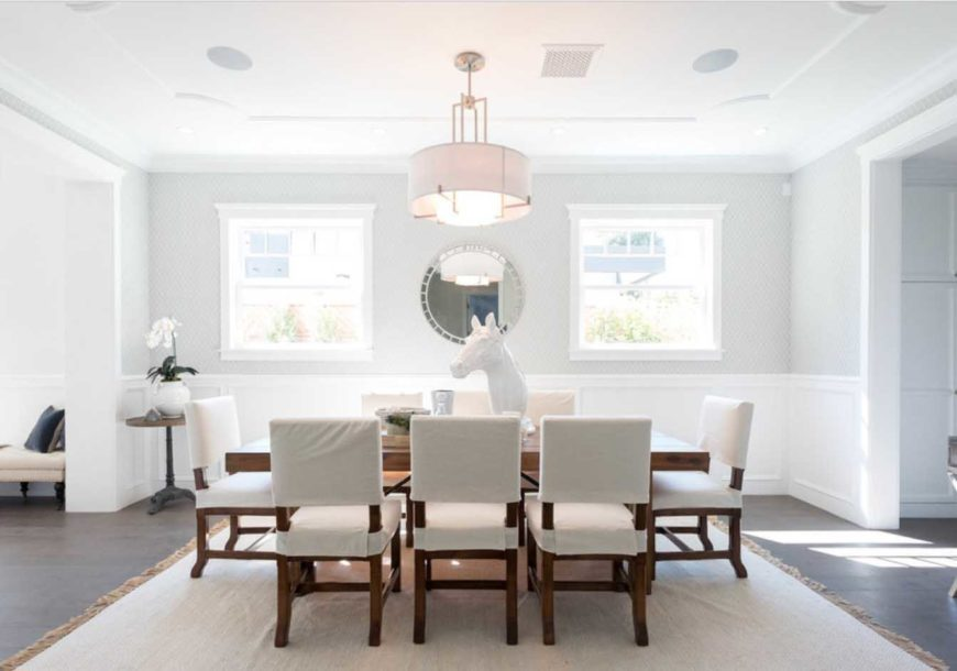Dining room featuring a modern clean look with white and muted gray walls, a wooden table, white cushioned chairs, a brown rug, tabletop decor and a drum shade chandelier.