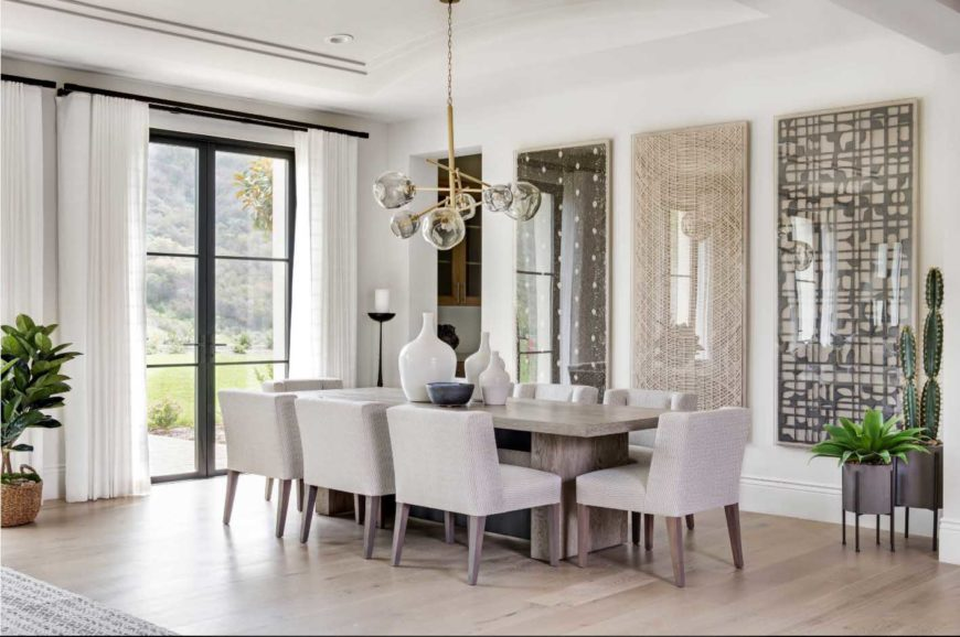 A relaxing dining room with rectangular wooden table, gray cushioned chairs and three huge wall art decor. It also has a brass globe chandelier which is an eye-catcher and indoor plants which refreshes the room.