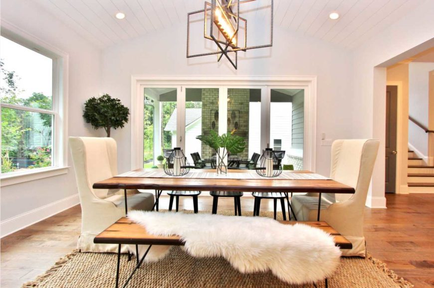 A chic dining room with cove ceiling, a statement chandelier, wooden table with three chairs, two white wingback chairs and a bench with a white fur throw blanket.