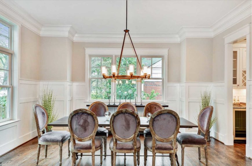 A spacious dining room with crown molding and wainscoting, a rectangular wooden table with vintage chairs and an industrial chandelier.