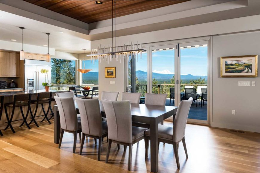 A warm dining area with a gray tone. It has a dark wooden table with gray upholstered chairs, hardwood flooring, wall paintings, a unique rectangular chandelier hanging on a wooden ceiling and a glass door with a perfect view of the mountain.