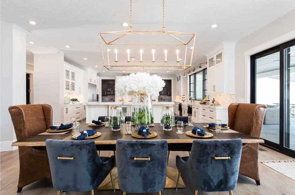 White dining room with a wooden table, six blue chairs and two brown large chairs on each side, hardwood flooring and a rectangular rustic chandelier.