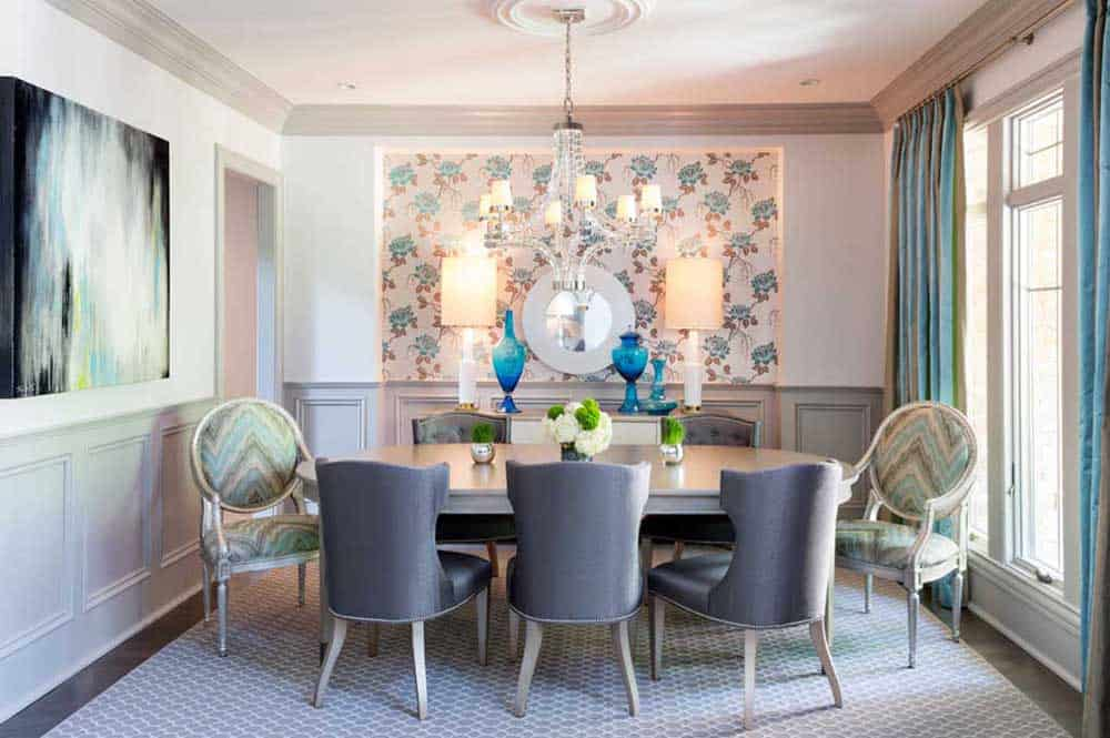 Pastel colors added a fresh look on this mini dining room. It has an oval wooden table, upholstered chairs, a patterned rug, an abstract painting, desk lamps and a lovely crystal chandelier.