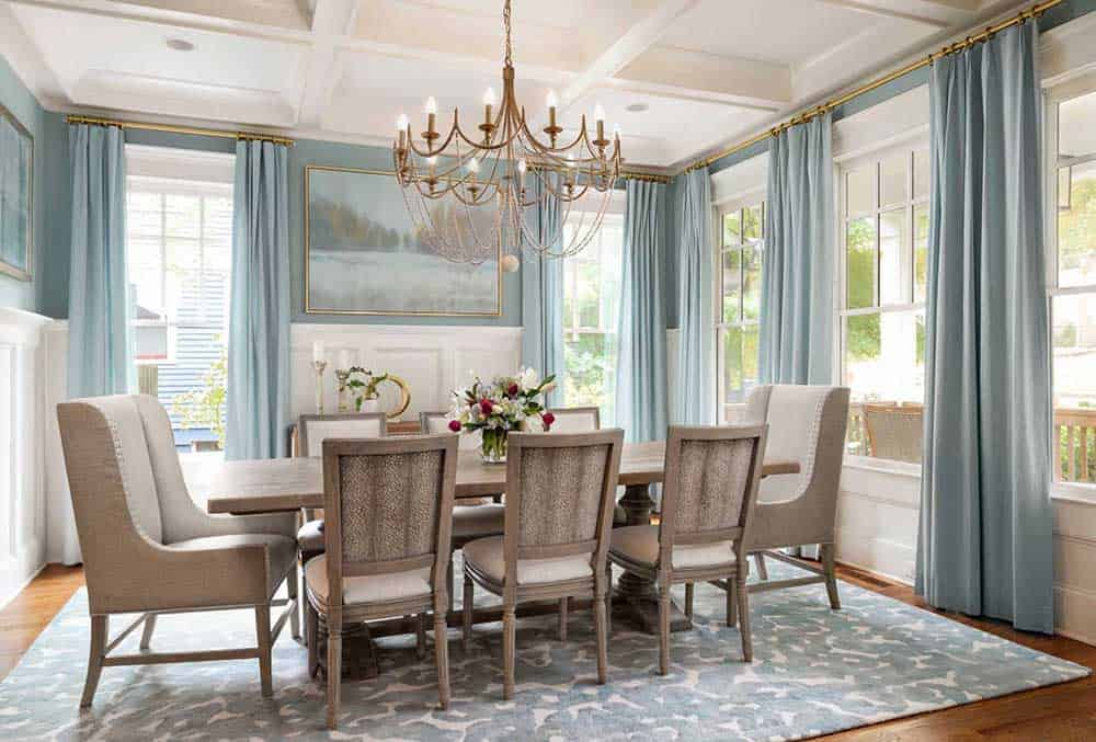 Pastel blue walls and curtains, a wooden table with six upholstered chairs and two wingback cushioned chairs, a printed soft rug and a gold candle chandelier that adds an elegant vibe to this cool dining room.