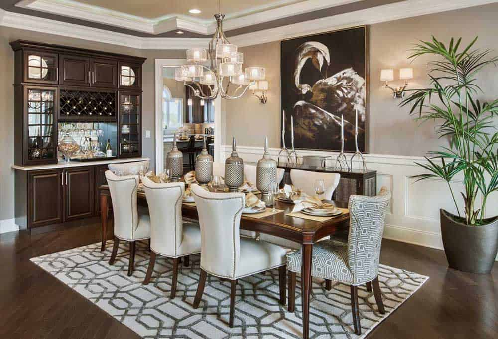 Classic dining room with china cabinet, a wooden table, upholstered chairs, a patterned rug, a painting with wall lamps on each side, an elegant chandelier and a huge indoor plant that refreshes the area.