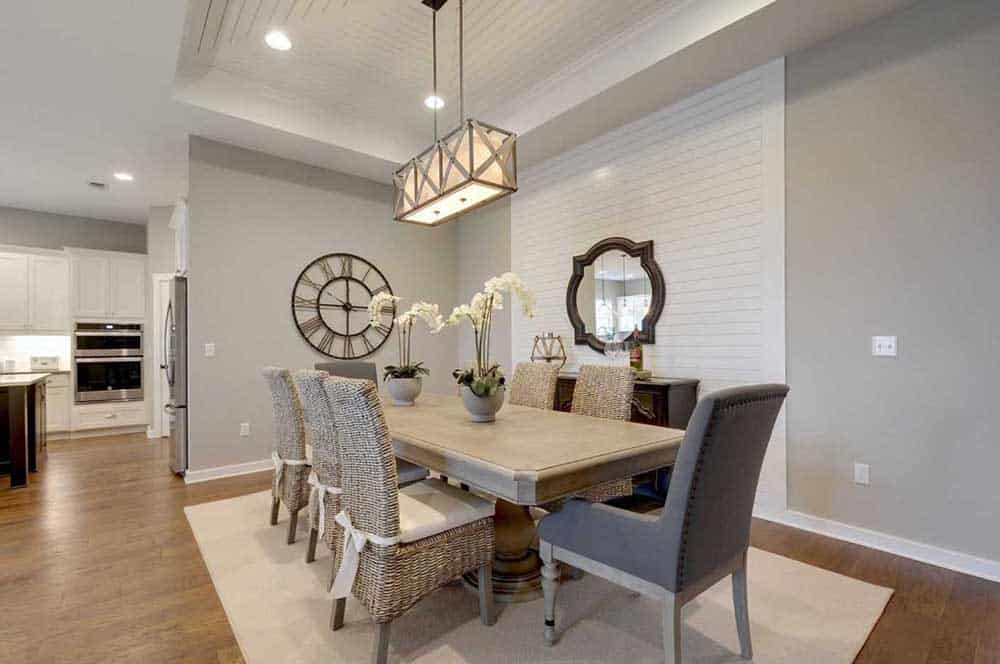 Dining area with a rectangular table, six rattan chairs and two upholstered chairs on each ends,  gray walls with an accent white stripes wall complementing the ceiling, wall clock and mirror and a rectangular chandelier.
