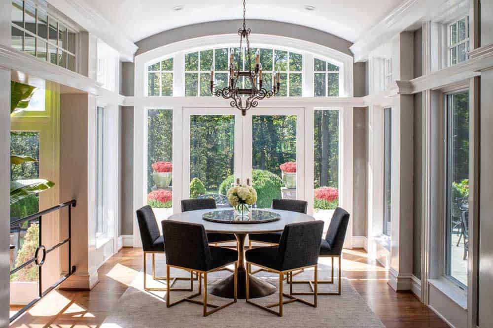 A small dining area with a round table surrounded by six black chairs, a vintage chandelier and a glass door and window.