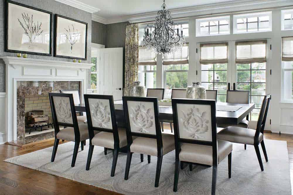 A white and gray toned dining room with a fireplace, a rectangular wooden table with ten chairs and an elegant chandelier.