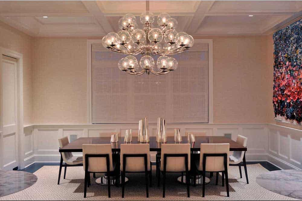 A classy dining room with a stunning chandelier, rectangular table with unique centerpieces and cream chairs topped with an oversized rug.