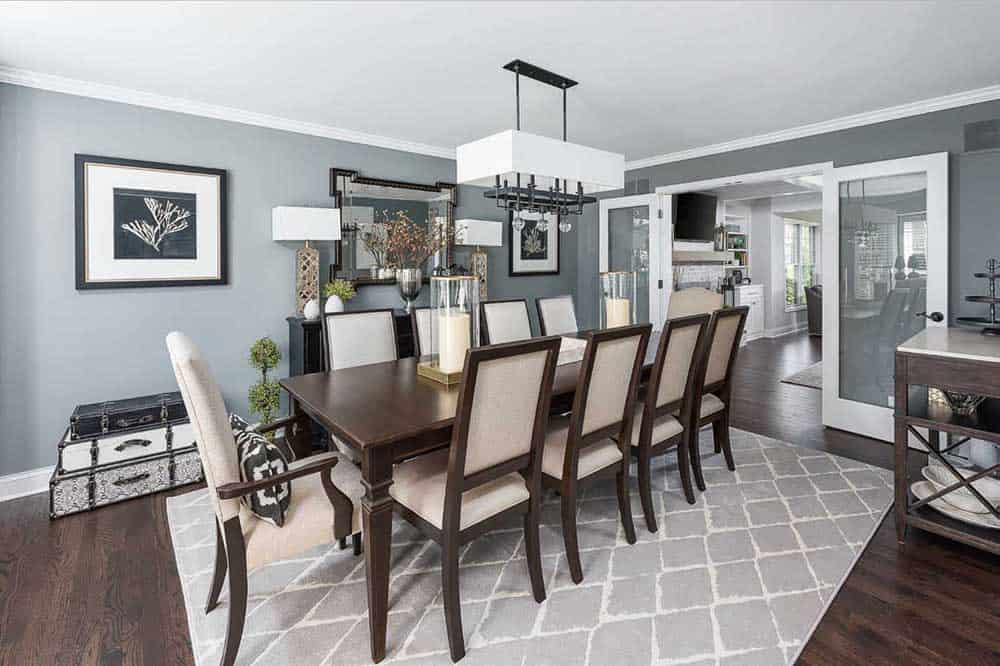 A dining area with beautiful gray and white color combination walls, hardwood flooring, rectangular wooden table, upholstered chairs, a gray patterned rug, desk lamps and a modern chandelier.