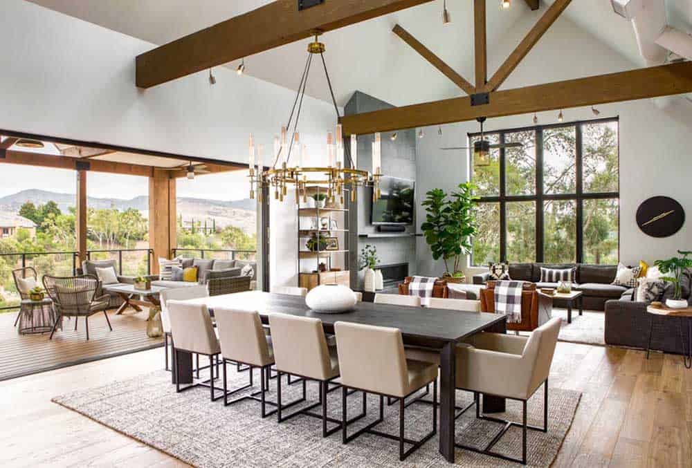 Fresh dining room with a touch of greeneries, wood beam ceiling with a huge candle chandelier, 10-seater dining table, a rug and hardwood flooring.
