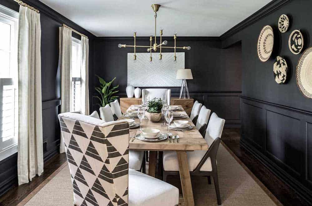 A black dining room with wooden table, upholstered chairs, a brown rug, fancy round wall decors and a modern chandelier.