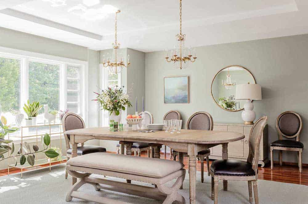 A dining room with an oval wooden table, six chairs and an upholstered bench, gold round wall mirror, Victorian chandeliers, live plants and a large glass window that brings the natural light making the room brighter and livelier.