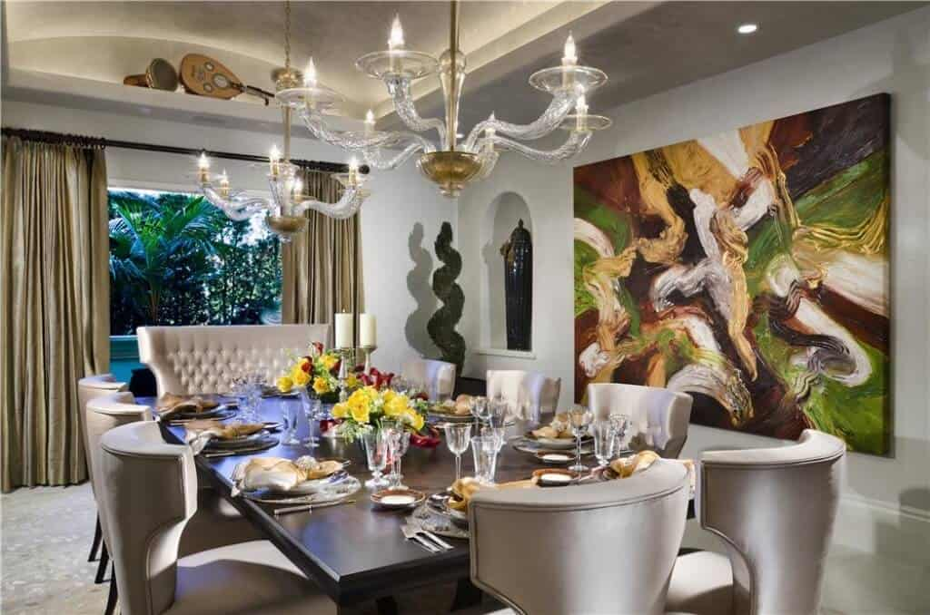 This elegant formal dining room has silver cushioned wing back chairs surrounding a long dark wooden dining table that is adorned with a couple of elegant chandeliers and a large colorful painting on one side.
